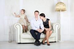 Il padre, la madre e la piccola figlia sveglia si siedono al sofà Immagini Stock Libere da Diritti