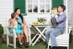 Il padre, la madre, il bambino e la figlia si siedono alla tavola Fotografie Stock