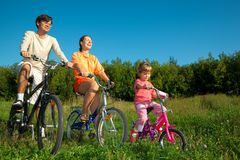 Il padre, la mummia e la figlia vanno per azionamento sulle biciclette Fotografia Stock