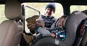 Il padre mette sopra lo stivale del bambino nell'interno dell'automobile archivi video