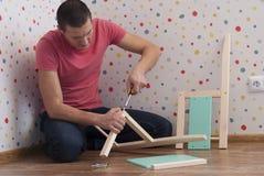 Il padre monta una sedia per i bambini immagine stock