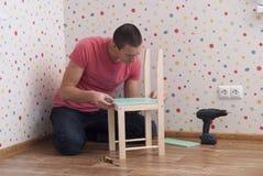 Il padre monta una sedia per i bambini fotografie stock