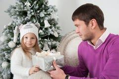 Il padre presenta il regalo a sua figlia al Natale Fotografia Stock