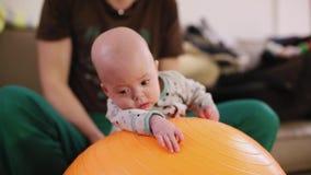 Il padre rotola neonato sul massaggio di sport della palla di forma fisica archivi video