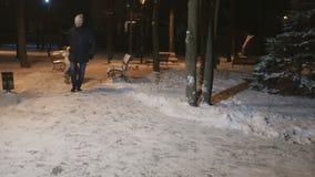 Il padre rotola una moglie con la piccola figlia sulla slitta nel parco dell'inverno di sera stock footage