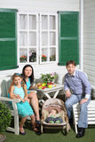 Il padre sorridente, la madre, il bambino e la piccola figlia si siedono alla tavola Fotografia Stock
