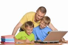 Il padre sta aiutando i bambini con compito Fotografie Stock