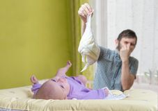 Il padre sta cambiando i pannolini puzzolente Cura del bambino con diarrea Fotografia Stock