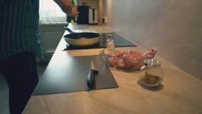 Il padre sta cucinando le bacchette di pollo per i suoi bambini per la cena video d archivio