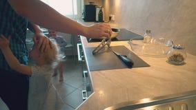 Il padre sta cucinando le bacchette di pollo per i suoi bambini per la cena archivi video
