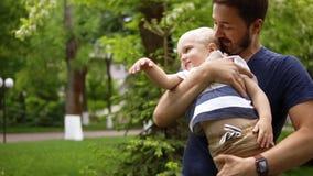 Il padre sta giocando con il suo piccolo, figlio blondy all'aperto Tenuta lui nelle sue armi, giocanti Poi lo bacia e mettono sop stock footage