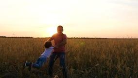 Il padre tiene il figlio nelle sue armi e si gira con lui Siluetta di una famiglia felice contro il tramonto archivi video
