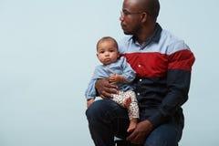 Il padre tiene la sua piccola figlia del bambino sul suo ginocchio contro fondo blu-chiaro fotografia stock