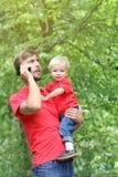 Il padre tiene suo figlio del bambino nelle suoi armi e colloqui su uno smartphone Papà e bambino all'aperto Abbigliamento di sgu Immagine Stock Libera da Diritti
