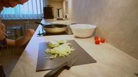 Il padre in una camicia a strisce sta cucinando l'insalata di verdure organica fresca, il cibo sano per i bambini stock footage