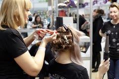 Il padrone dei capelli fa un'acconciatura complessa con un'ondata di capelli a fotografie stock