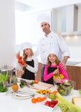 Il padrone del cuoco unico e l'allievo minore scherzano le ragazze a cucinare la scuola Fotografia Stock