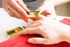 Il padrone del manicure fa il manicure sulla mano della giovane donna fotografia stock