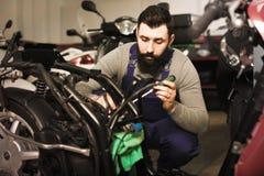 Il padrone di funzionamento cattura i dettagli su una motocicletta Fotografie Stock Libere da Diritti