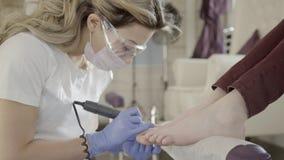 Il padrone di pedicure sta lucidando esattamente i chiodi del dito del piede dei clienti facendo uso della macchina in salone di  video d archivio