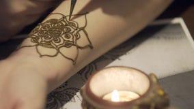 Il padrone disegna il mehendi sulla mano del ` s della ragazza Bei modelli da hennè Fiori da hennè sulle mani Su tiraggio delle m archivi video