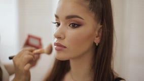Il padrone femminile di trucco usa una spazzola della polvere Bello modello nello studio di bellezza Modo professionale di rivest video d archivio