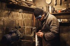 Il padrone frantuma il coltello su una smerigliatrice della cinghia e molte scintille sono prodotte immagine stock libera da diritti