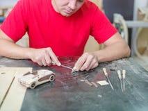 Il padrone raccoglie un modello di legno dell'automobile Immagini Stock
