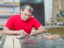 Il padrone raccoglie un modello di legno dell'automobile Immagini Stock Libere da Diritti