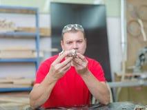 Il padrone raccoglie un modello di legno dell'automobile Fotografia Stock Libera da Diritti