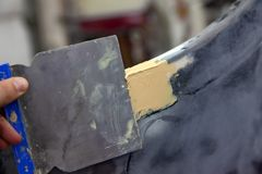 Il padrone sul lavoro in un'officina dell'automobile applica un mastice con un rivestimento per riempire di malta un paraurti ric fotografia stock