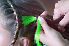 Il padrone tesse un filo colorato nel girl& x27; treccia di s immagine stock