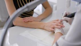 Il padrone utilizza una macchina elettrica per rimuovere lo smalto sulle mani durante il manicure nel salone video d archivio