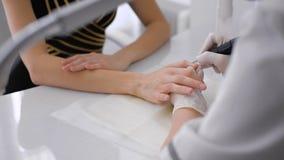 Il padrone utilizza una macchina elettrica per rimuovere lo smalto sulle mani durante il manicure nel salone stock footage
