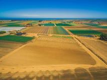 Il paesaggio aereo dei campi arati ed i raccolti si avvicinano alla linea costiera dell'oceano Immagine Stock
