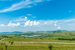 Il paesaggio agricolo dell'estate, asfalta la strada rurale su priorità alta, i laghi enormi, piccolo villaggio Fotografie Stock