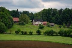 Il paesaggio alpino rurale con il villaggio sloveno in valle vicino ha sanguinato il lago al giorno soleggiato della molla sloven Immagine Stock