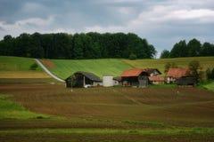 Il paesaggio alpino rurale con il villaggio sloveno in valle vicino ha sanguinato il lago al giorno soleggiato della molla sloven Fotografie Stock Libere da Diritti