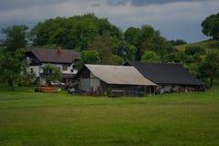 Il paesaggio alpino rurale con il villaggio sloveno in valle vicino ha sanguinato il lago al giorno soleggiato della molla sloven Fotografia Stock