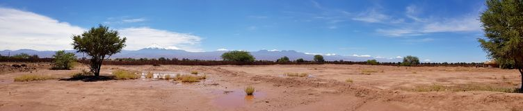 Il paesaggio arido e desolato del deserto di Atacama ed i picchi dei vulcani nevosi delle Ande Cordigliera nel backgrou immagine stock