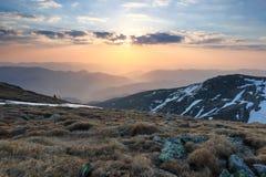 Il paesaggio con i prati, le alte montagne ed i picchi coperti di neve Un uomo in photocamera è si siede al bordo della voragine fotografie stock libere da diritti