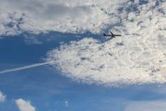 Il paesaggio con l'aeroplano bianco sta volando nel cielo blu sopra le nuvole fotografia stock
