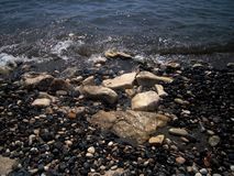 Il paesaggio del mare, le pietre di Mar Nero e di bianco ed il ciottolo e lo scintillio ondeggiano fotografia stock