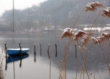 Il paesaggio dell'inverno con i ciuffi nevosi di erba e della barca ha attraccato la o fotografia stock libera da diritti