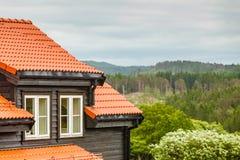 Il paesaggio della foresta, alloggia il tetto rosso in priorità alta Immagini Stock