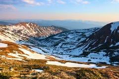 Il paesaggio delle alte montagne in neve L'erba e le rocce sul prato L'alba sta alleggerendo l'orizzonte Immagine Stock Libera da Diritti