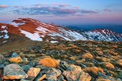 Il paesaggio delle alte montagne in neve L'erba e le rocce sul prato L'alba sta alleggerendo l'orizzonte Fotografia Stock Libera da Diritti