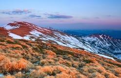 Il paesaggio delle alte montagne in neve L'erba e le rocce sul prato L'alba sta alleggerendo l'orizzonte Immagine Stock