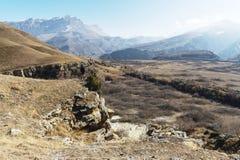 Il paesaggio fuori stagione delle montagne del Caucaso un giorno soleggiato un uomo sull'orlo di una scogliera che guarda fuori i Fotografie Stock Libere da Diritti