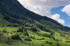 Il paesaggio idilliaco nelle alpi nella primavera con il chalet tradizionale della montagna e la montagna verde fresca pascola co Fotografie Stock